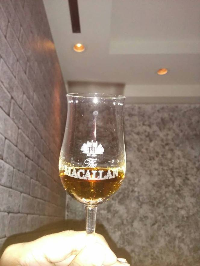 A glass of The Macallan Rare Cask, presented in a sturdy Macallan-branded copita glass.